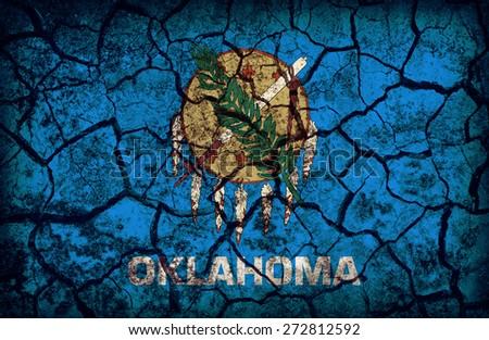 Oklahoma flag pattern on crack soil texture,retro vintage style - stock photo