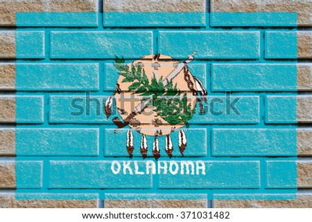 Oklahoma state flag of America on brick wall - stock photo