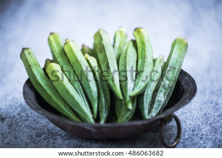 Okra in rustic bowl on slate background
