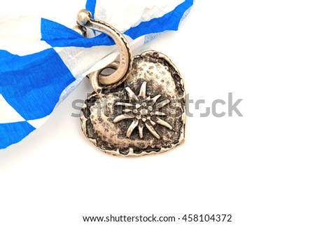 Oktoberfest background with  Bavarian ribbon and Silver pendant in horseshoe and heart shape with  Edelweiss on white background,  text place