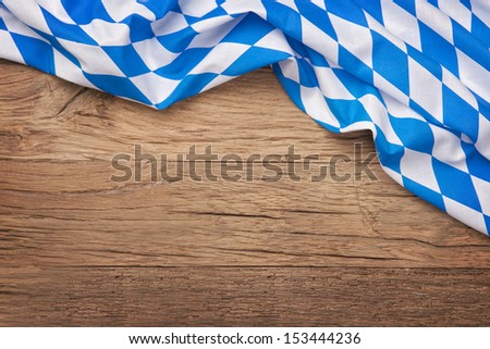 Oktoberfest blue checkered fabric on wooden background - stock photo