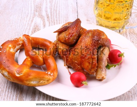 Oktoberfest chicken with pretzel, beer and radish, close up - stock photo