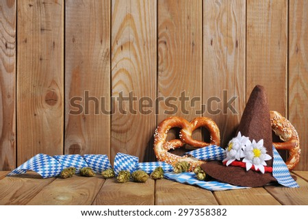 Oktoberfest - original bavarian Oktoberfesthat and soft pretzels from Germany in front of olt wooden board - stock photo