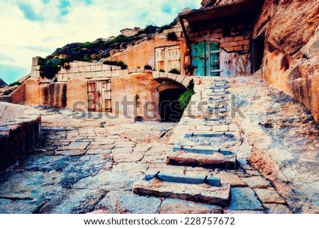 Old abandoned boat houses built into the Cliffside in Dwejra, Gozo - stock photo