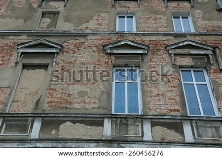 Old abandoned building with windows in old town - stock photo