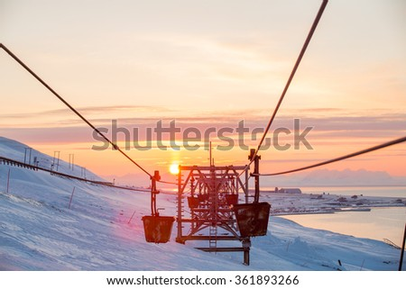 Old abandoned coal cableway in the rays of the setting sun in the town of Longyearbyen among snow-capped mountains of the Norwegian archipelago of Svalbard. - stock photo