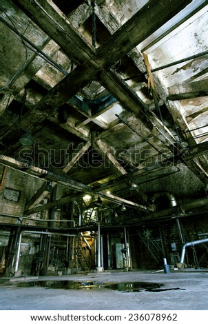Old abandoned dirty empty scary factory interior - stock photo