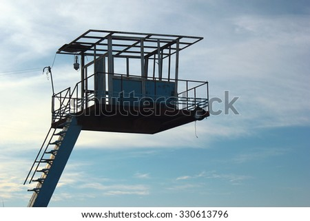 old abandoned empty lifeguard booth on blue sky background - stock photo