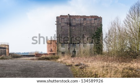 Old abandoned factory building and rusty storage tanks at a Belgian industrial area. - stock photo