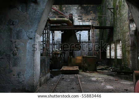 Old abandoned factory with useless rusty machinery - stock photo