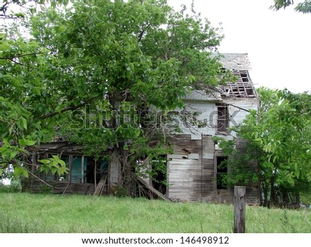 old abandoned farm buildings house hidden in trees - stock photo