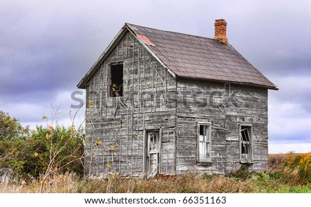 Old abandoned farmhouse in the middle of a storm - stock photo