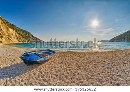 Old Abandoned Fishermen Boat at Empty Sunset Myrtos Beach in Kefalonia, Greece - stock photo