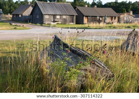 Old abandoned fishing boat an fishing cabins at the coast of Gotland, Sweden. Vitvaers fishing harbour. - stock photo