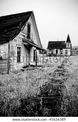 old abandoned house and church with broken, overgrown footpath - stock photo