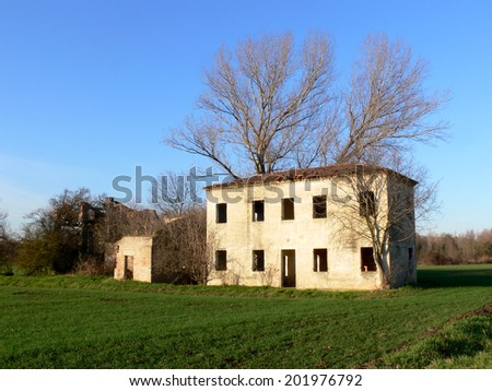Old abandoned house in a rural meadow  - stock photo