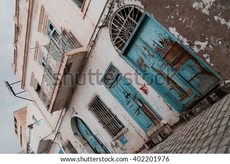 Old abandoned house on the street with balcony and blue wooden windows and doors. French colonial architecture. Inclined composition. Tunisia - Sousse. - stock photo