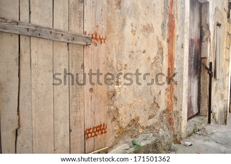 Old abandoned house with wooden doors - stock photo