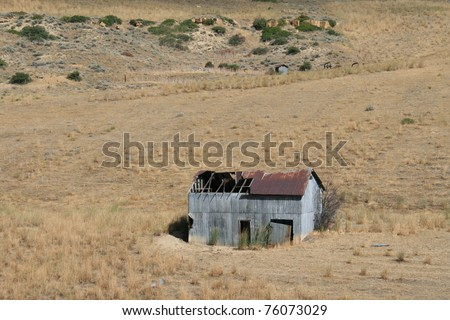 Old Abandoned metal building on a hillside - stock photo