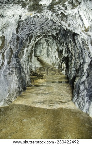 Old abandoned mine tunnel with aragonite coatings - stock photo