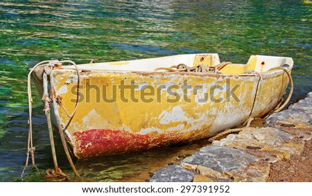 Old abandoned moored rowing boat  - stock photo