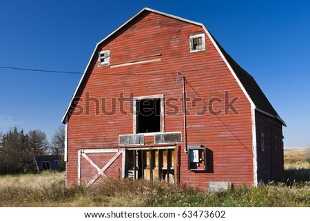 Old abandoned red barn on the prairies of Canada. - stock photo