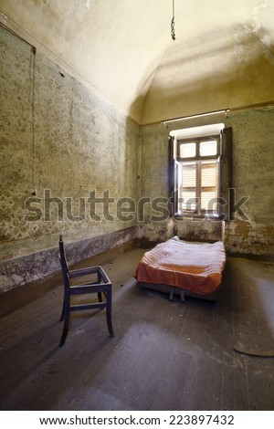 old abandoned room with bed and chair - stock photo