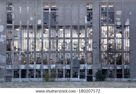 Old abandoned rundown gray facade of glass windows. - stock photo