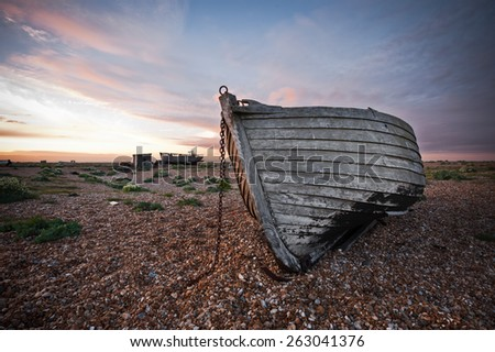 Old abandoned wooden boat on pebble beach - stock photo