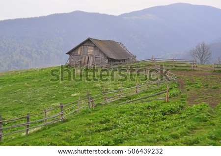 Old abandoned wooden house in the mountains. Surrounded by wooden rustic fence