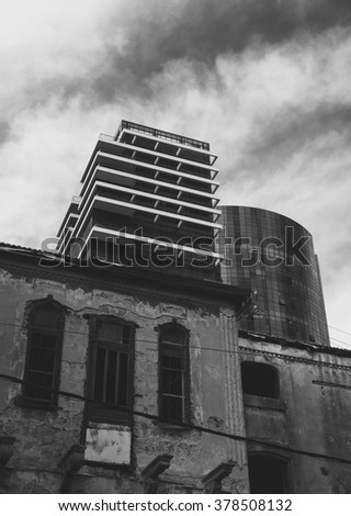 Old abandoned wrecked house and modern building at backgrounds. Tel Aviv (Israel). Time concept. Dark aged photo. Black and white. - stock photo