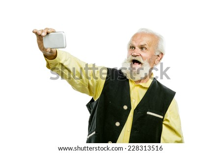 Old active bearded man taking selfie with mobile phone isolated on white background - stock photo