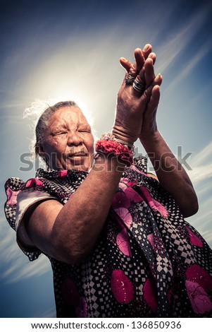 old african homeless woman deep in prayer with the sky as a background - stock photo