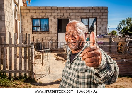 old african man showing thumbs-up in front of his house in the township