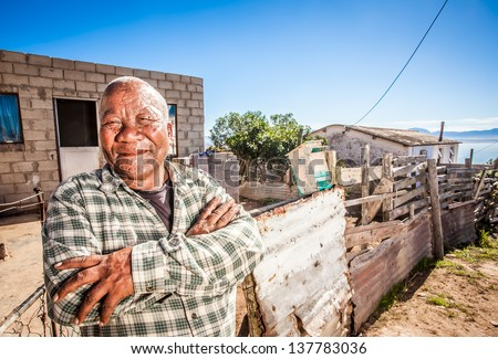 old african man standing proudly with his arms crossed in front of his home - stock photo