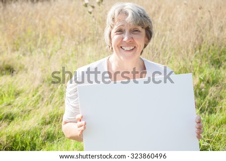 Old age woman holding blank white sign - stock photo