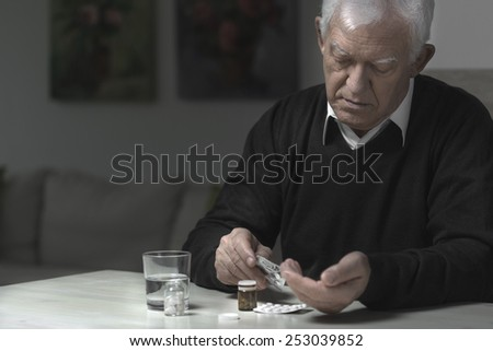 Old aged and sad man taking medicaments - stock photo