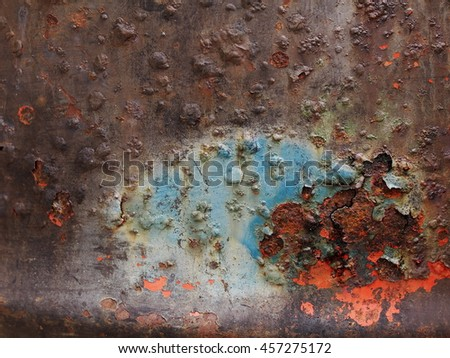 Old aged weathered rusty abandoned rustic uneven textured painted steel iron surface of a large metal water container cylinder form outdoor with holes and water leaks - stock photo
