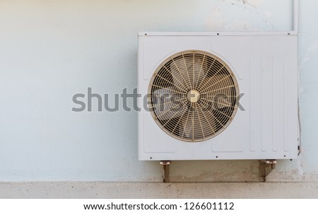Old air compressor is located outside office building - stock photo