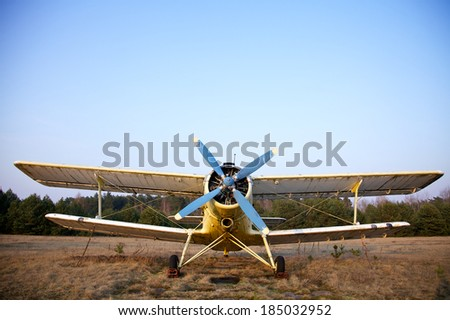 old airplane on green grass and sunset background - stock photo