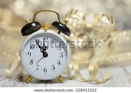 Old alarm clock set to five to midnight. Happy New Year! - stock photo