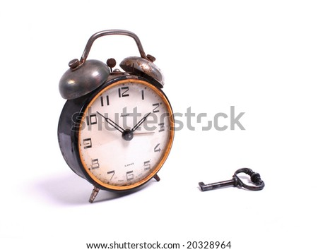 old alarm-clock with a key - stock photo