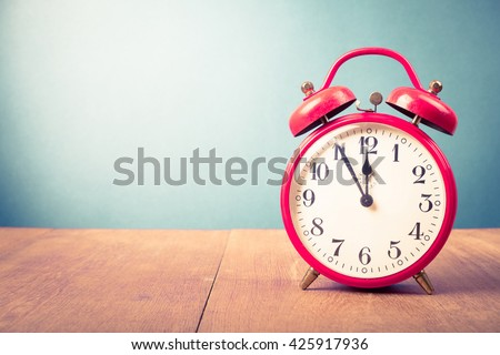 Old alarm clock with five minutes to twelve o'clock. Retro style filtered photo - stock photo