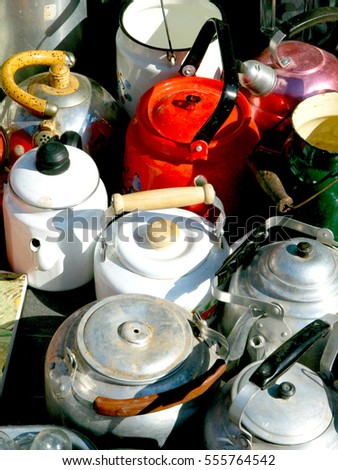 Old aluminum and enameled colorful kettles in retro style at flea-market