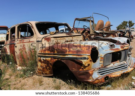 old american car in a junkyard - stock photo
