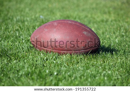 old American football ball on green grass - stock photo