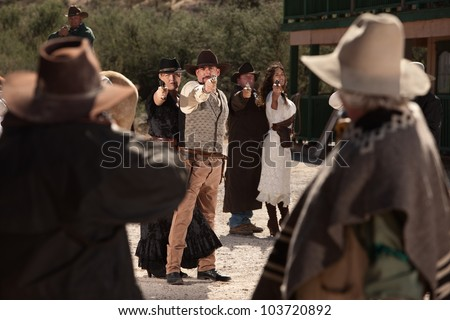 Old American west shoot out on dusty street - stock photo