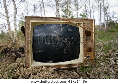 Old analog discarded television set in the forest