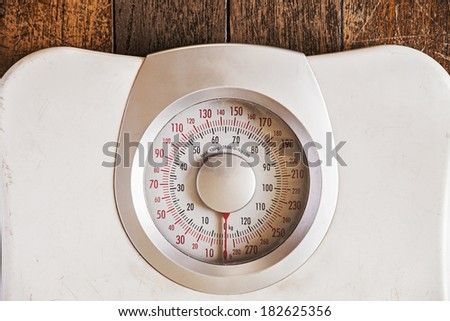 Old analog weight scale isolated on wooden floor - stock photo