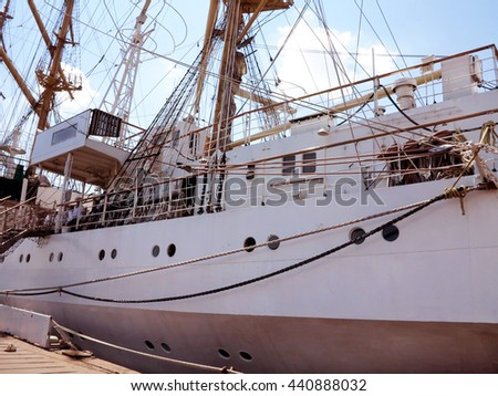 Old Ancient sailboat. Historic three-masted sailing ship without sails docked in harbor waterfront. Shaded view of fragment of  sailing schooner, as a background for creative design of tourist posters - stock photo